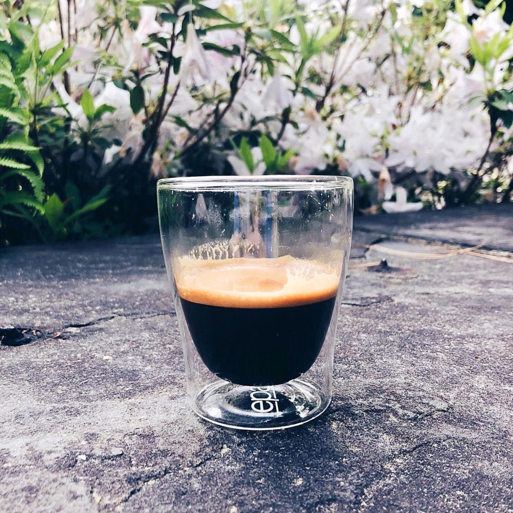 Espresso crema and flowers on pavement