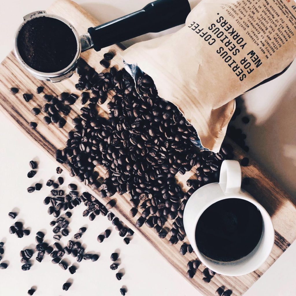coffee beans spilled with coffee mug and portafilter