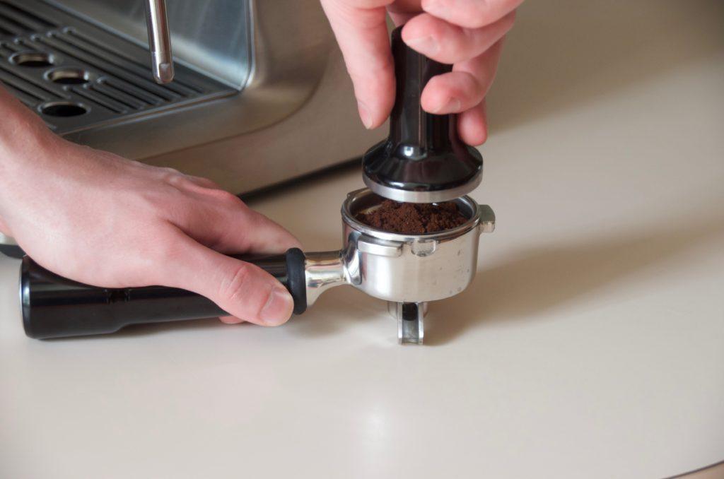 tamper and espresso grounds in portafilter