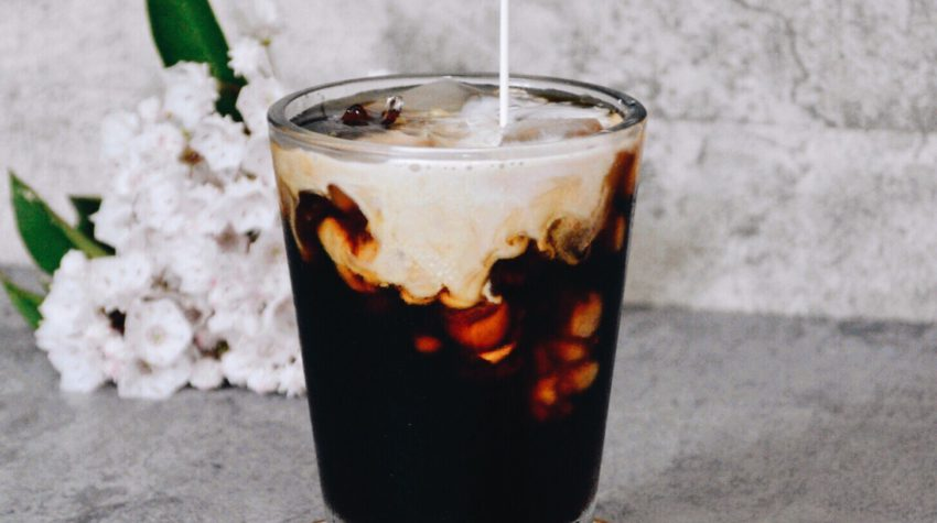 cold brew coffee with milk pouring from top and coffee ice cubes