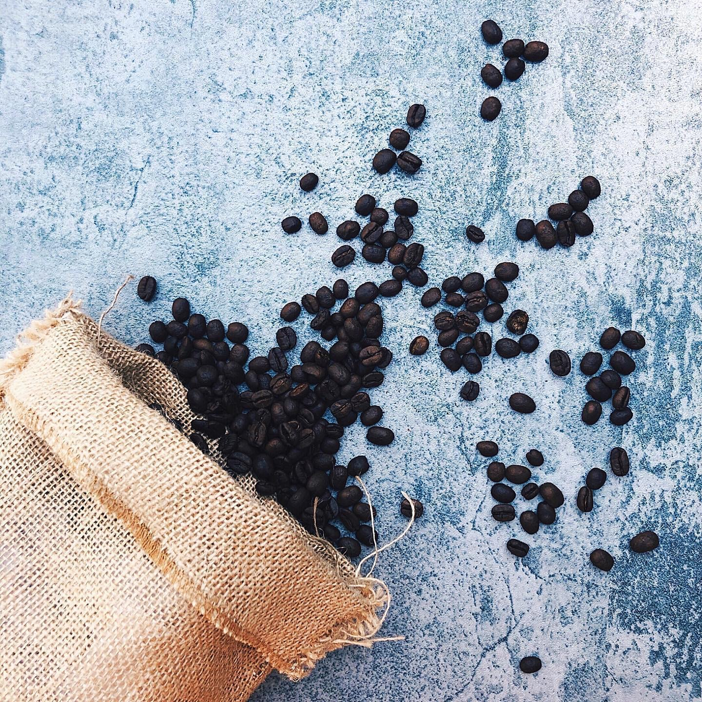 Coffee beans in burlap bag with blue background