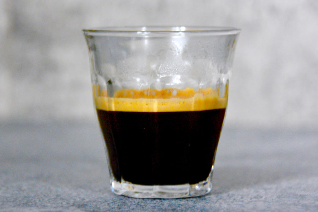 espresso shot on blue and gray background