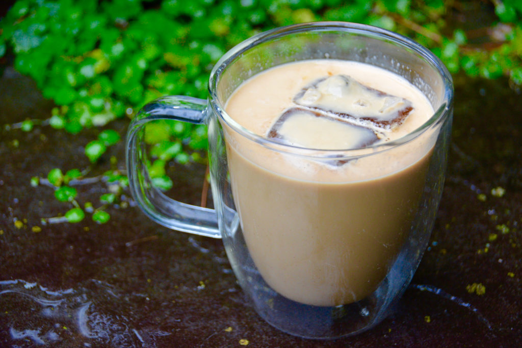 clear mug of iced coffee on pavement with greenery