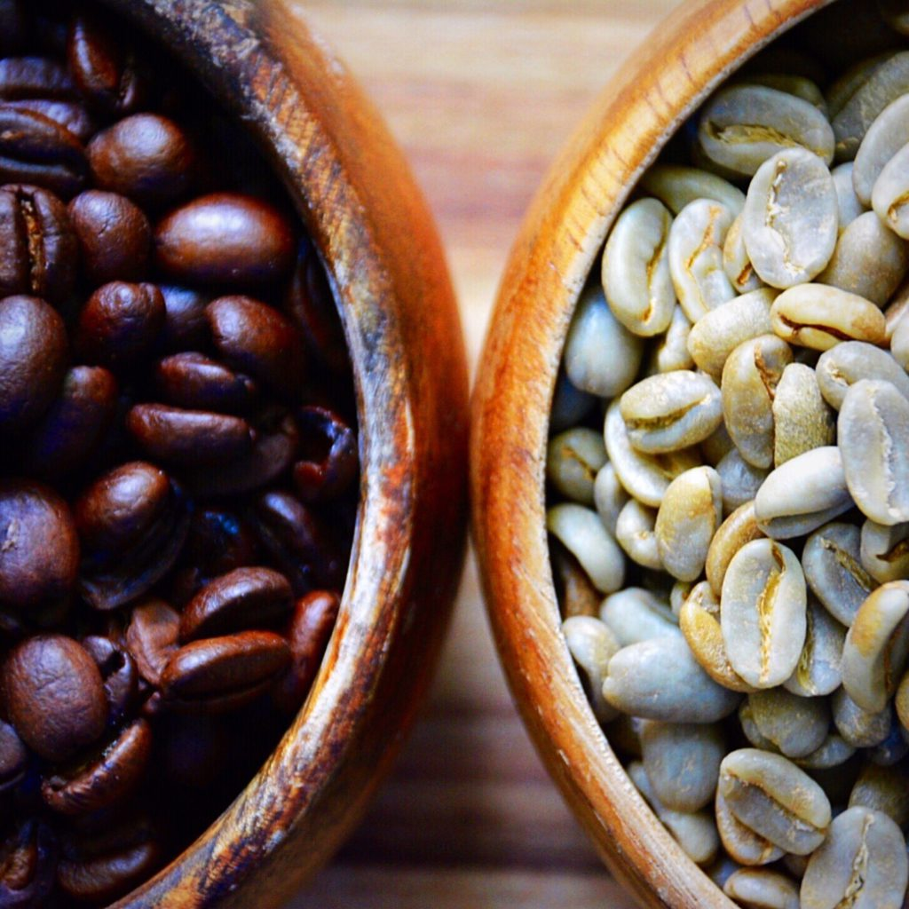 wooden bowls filled with green coffee beans and regular roasted coffee beans
