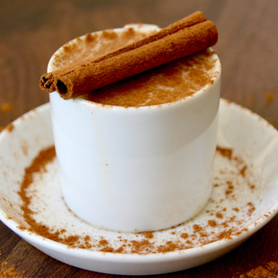 vanilla pumpkin spice latte in a small white coffee mug on a white saucer with cinnamon dusted on top and two cinnamon sticks as garnish