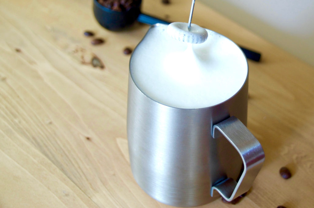 frothing milk in a server with an electric frother on a wooden background