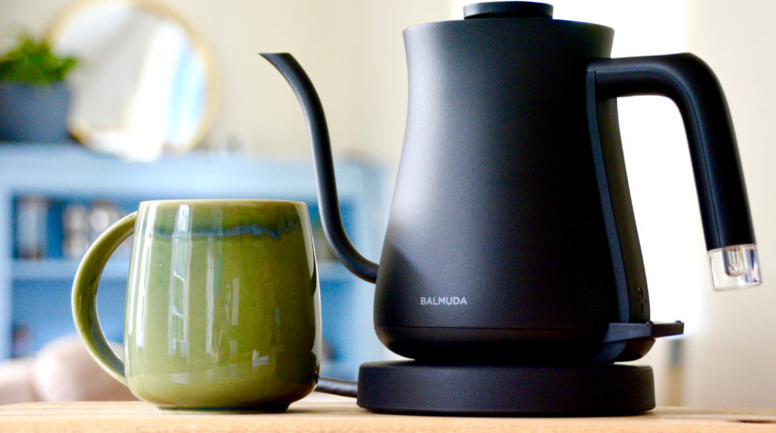 Balmuda the Kettle Black with green ceramic mug on a wooden table