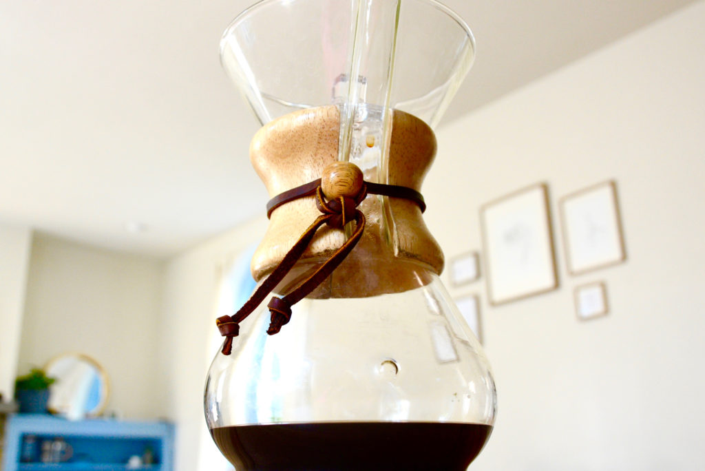Chemex filled with coffee on a table top
