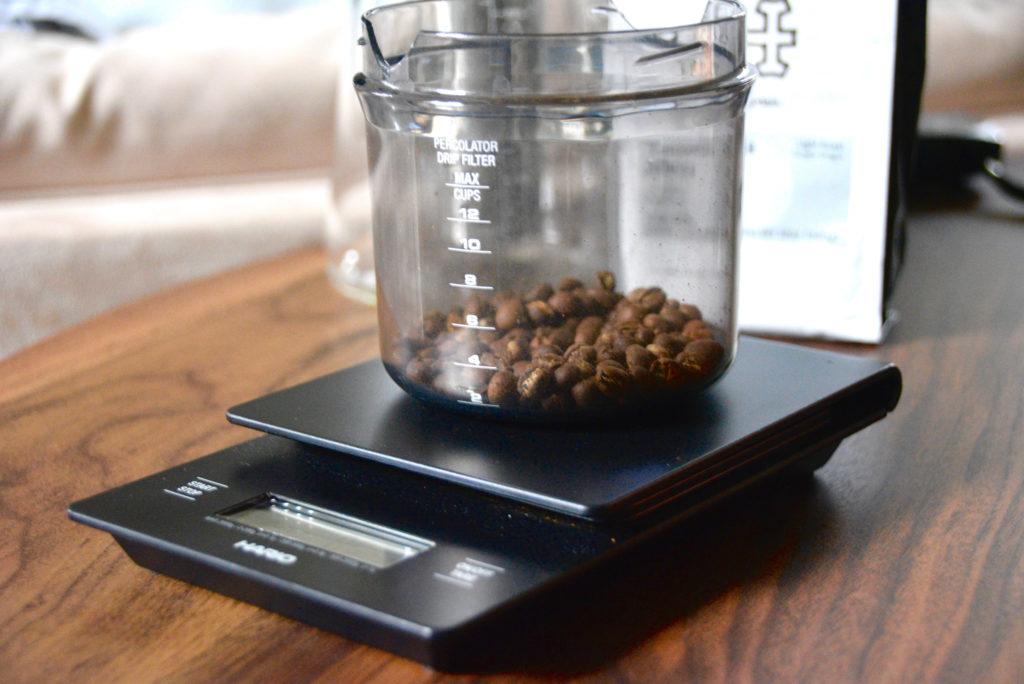 Hario scale with whole coffee beans being measured