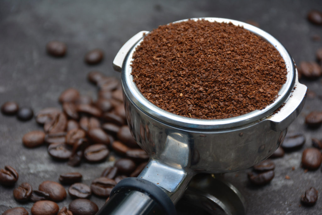 close up of ports filter with coffee grounds on pavement with coffee beans in background