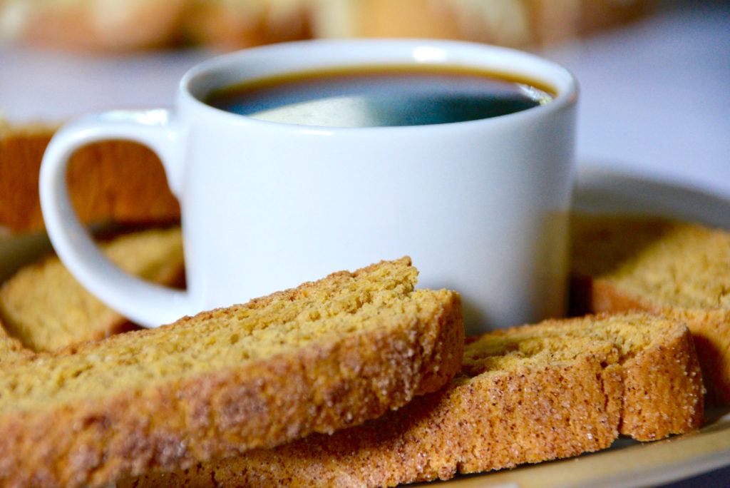 pumpkin biscotti on a plate surrounding a small cup of coffee in a white mug