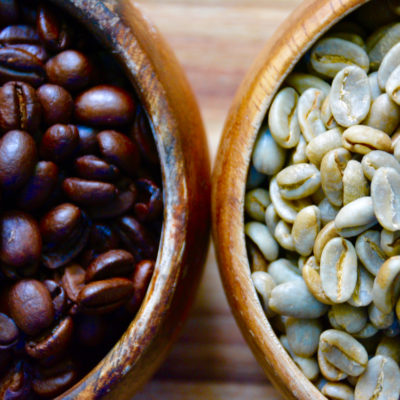 two wooden bowls filled with green beans and roasted coffee beans