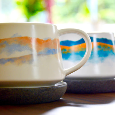 his and hers ceramic coffee mugs on a wood table with a floral background