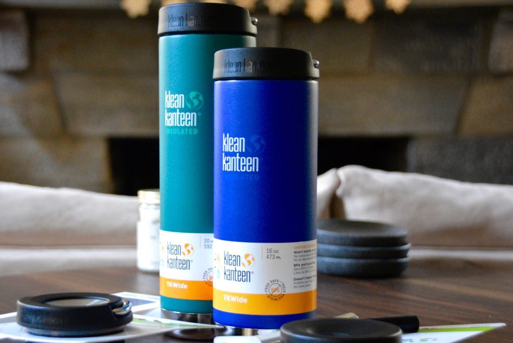 one blue and one teal klean kanteen insulated travel mugs on a wood table