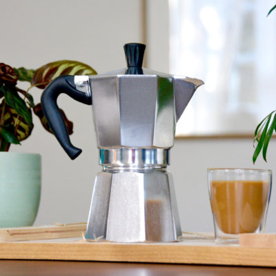 bialetti moka pot next to plants and a cup of coffee on wood table