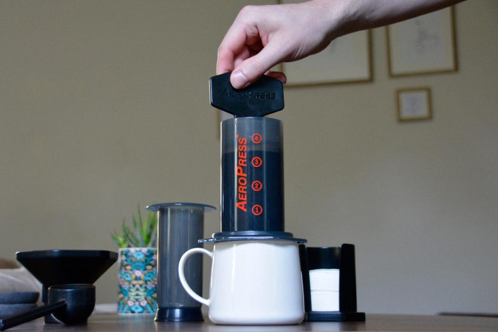 stirring grounds AeroPress on top of a white mug