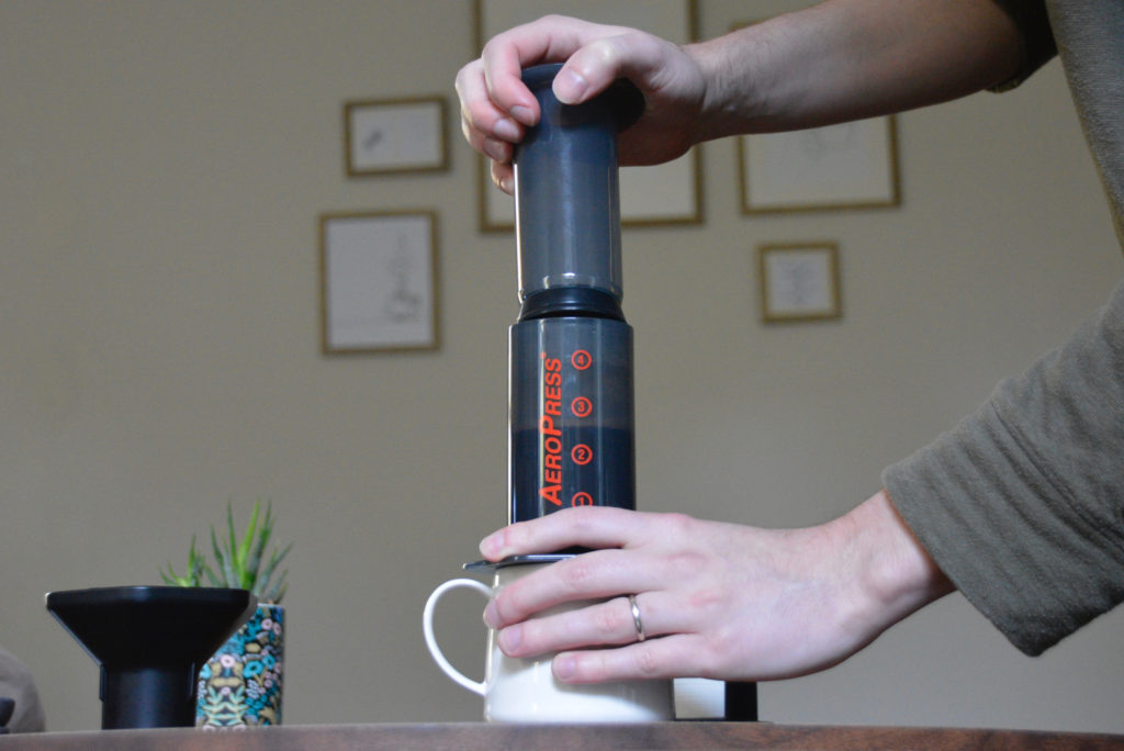 Pressing plunger of AeroPress into Chamber to brew coffee