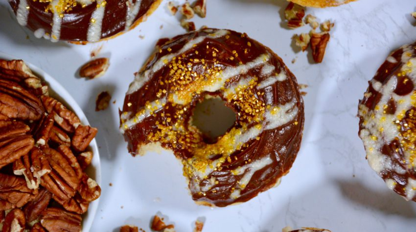 chocolate frosted donuts with gold and white and pecans