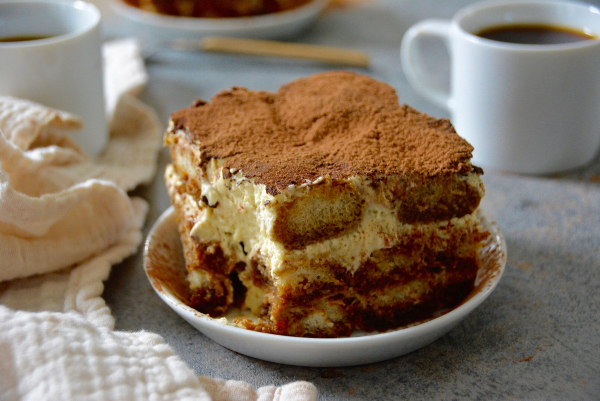 tiramisu on a plate with coffee cups in background