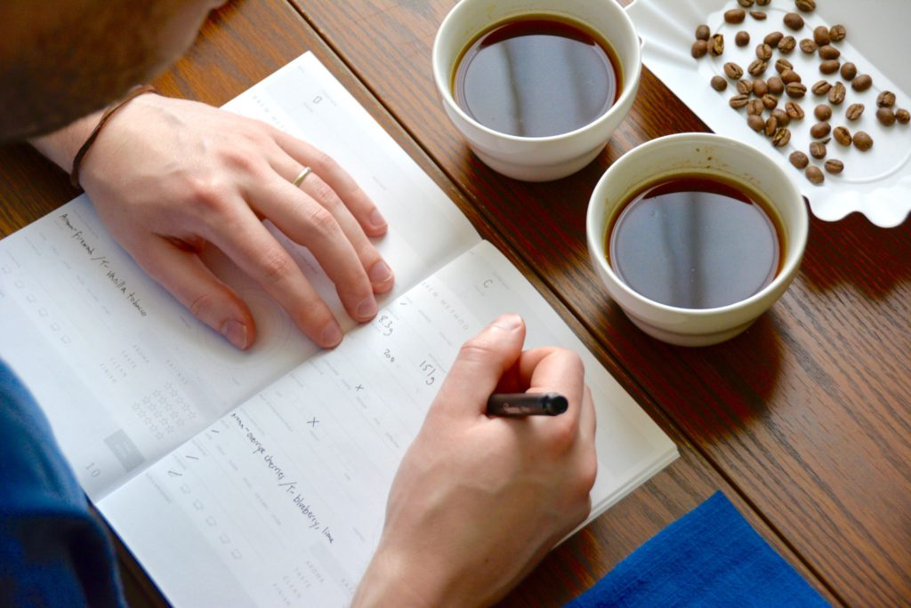 man writes in cupping form during a coffee cupping