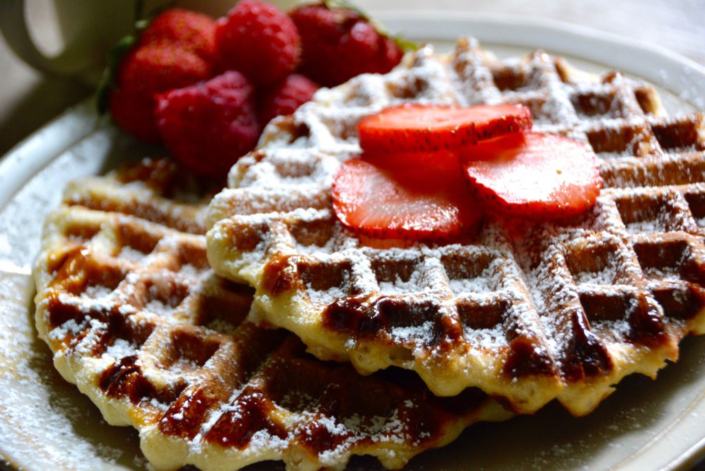 close up of belgian waffles with strawberries sliced