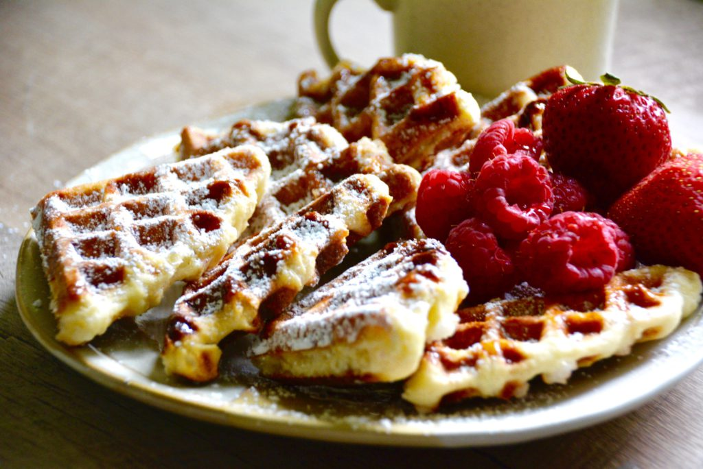Sliced Belgian waffles with fruit on a plate