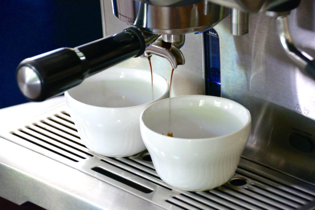 espresso machine with two white cups and espresso