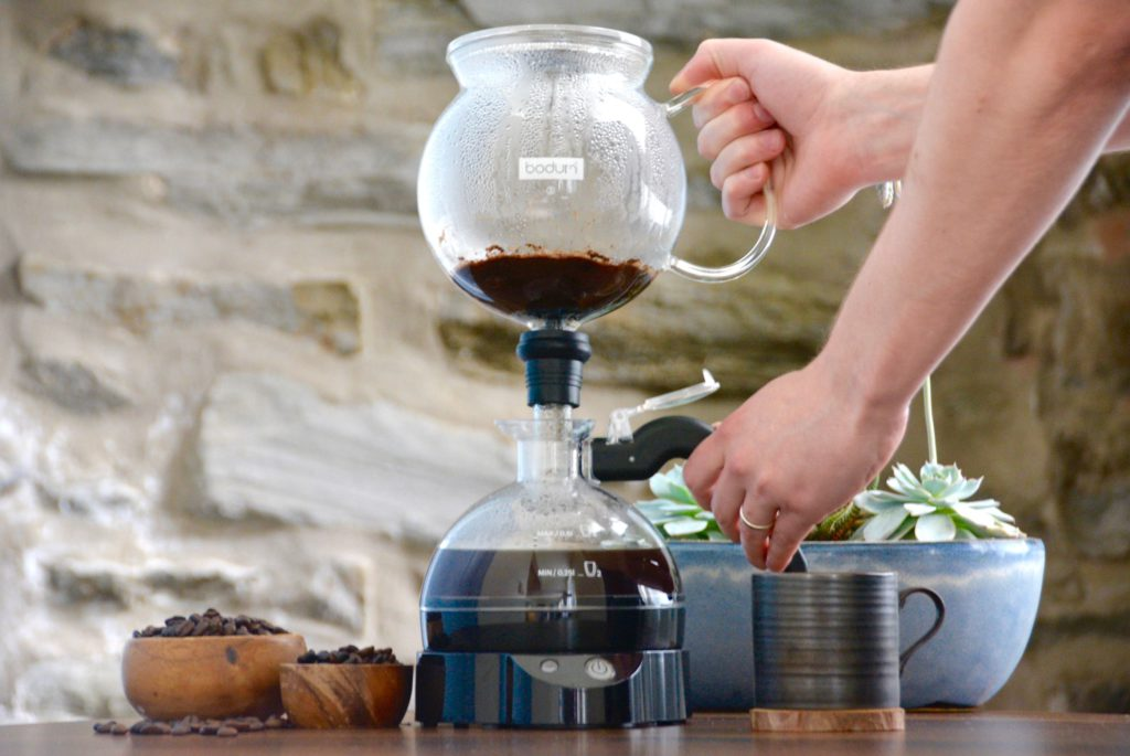 Bodum siphon coffee maker in use with upper and lower chamber
