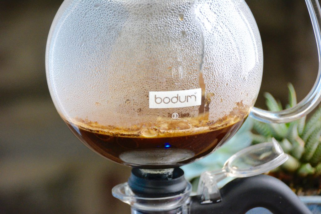 close up of upper chamber of a siphon coffee maker