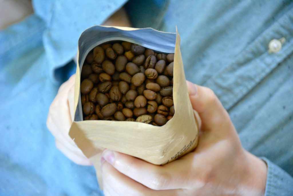 man holding bag of coffee beans on blue background