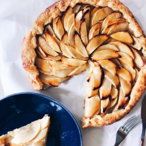 apple galette with a slice out of it on a blue plate next to it