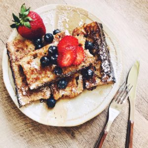 French toast with strawberries and blueberries on a light pink plate