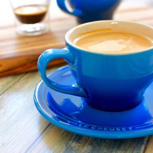 blue mug with coffee with espresso and blue mug behind it