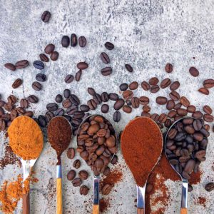 spoons with different coffee beans and roasts on blue background