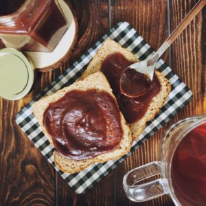 whole wheat bread with apple butter on a plaid plate and wood background