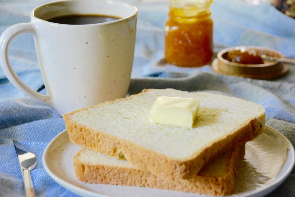 bread with butter and cup of coffee in speckled mug with orange marmalade in background