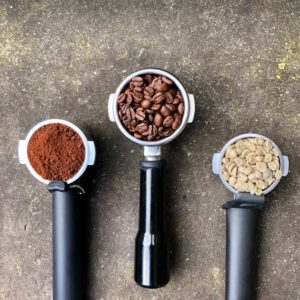 group heads with coffee beans and coffee grounds