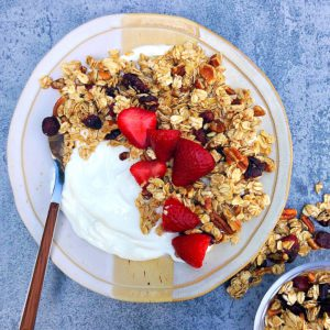 yogurt with granola and strawberries on a plate