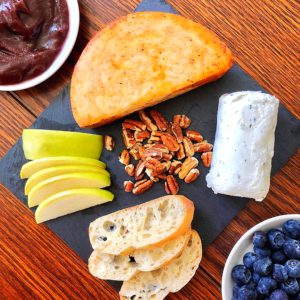 cheese plate with soft and hard cheese, fruits, nuts, and jam