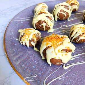 white chocolate covered cake truffles on a purple plate