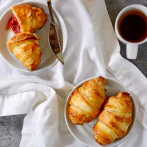 croissants on a white and blue background flat lay with cup of coffee