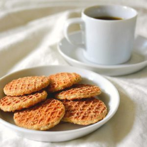 coffee with mini strop-waffles on a white sheet